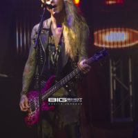 Lexxi Foxx of Steel Panther plays bass on stage at the Culture Room